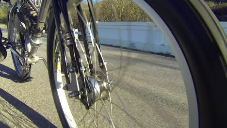 Close-up-of-the-wheels-of-a-motorized-bicycle-through-the-countryside-on-a-two-lane-road