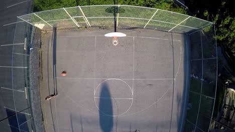 A-birds-eye-aerial-over-a-basketball-player-shooting-baskets-on-an-outdoor-court