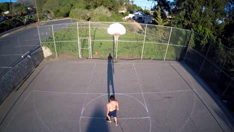A-birds-eye-aerial-over-a-basketball-player-shooting-a-free-throw-on-an-outdoor-court