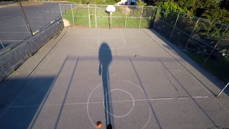 A-birds-eye-aerial-over-a-basketball-player-dribbling-on-an-outdoor-court