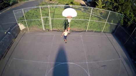 A-birds-eye-aerial-over-a-basketball-player-shooting-a-layup-on-an-outdoor-court
