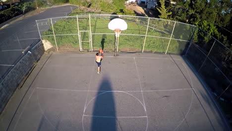 A-birds-eye-aerial-over-a-basketball-player-shooting-a-layup-on-an-outdoor-court-1
