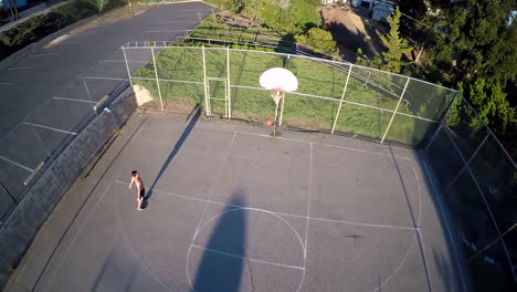A-birds-eye-aerial-over-a-basketball-player-shooting-a-jump-shot-on-an-outdoor-court