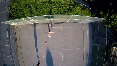 A-birds-eye-aerial-over-a-basketball-player-shooting-a-jump-shot-on-an-outdoor-court-1