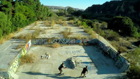 Aerial-shot-of-teenage-boys-skateboarding-in-the-graffiti-covered-foundation-of-an-abandoned-building