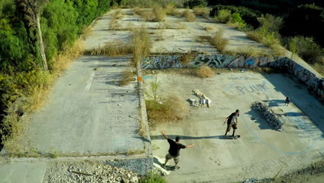 Toma-Aérea-De-Muchachos-Adolescentes-En-Patineta-En-Los-Cimientos-Cubiertos-De-Graffiti-De-Un-Edificio-Abandonado-1