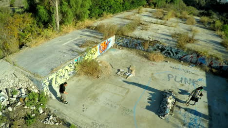 Aerial-shot-of-teenage-boys-skateboarding-in-the-graffiti-covered-foundation-of-an-abandoned-building-2