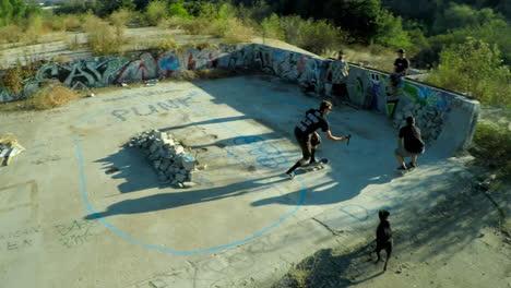 Toma-Aérea-De-Muchachos-Adolescentes-En-Patineta-En-Los-Cimientos-Cubiertos-De-Graffiti-De-Un-Edificio-Abandonado-3