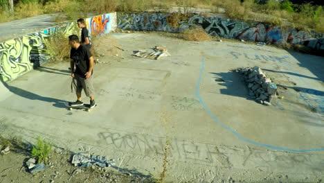 Toma-Aérea-De-Adolescentes-En-Patineta-En-La-Base-Cubierta-De-Graffiti-De-Un-Edificio-Abandonado-4
