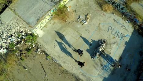 Toma-Aérea-De-Muchachos-Adolescentes-En-Patineta-En-Los-Cimientos-Cubiertos-De-Graffiti-De-Un-Edificio-Abandonado-5