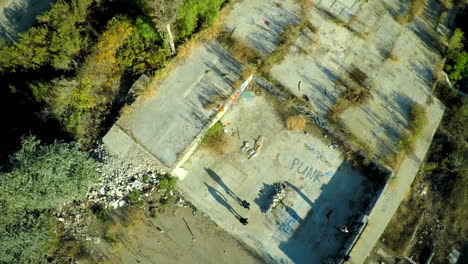 Aerial-shot-of-teenage-boys-skateboarding-in-the-graffiti-covered-foundation-of-an-abandoned-building-6