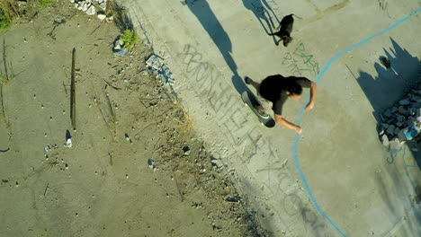 Aerial-shot-of-teenage-boys-skateboarding-in-the-graffiti-covered-foundation-of-an-abandoned-building-7