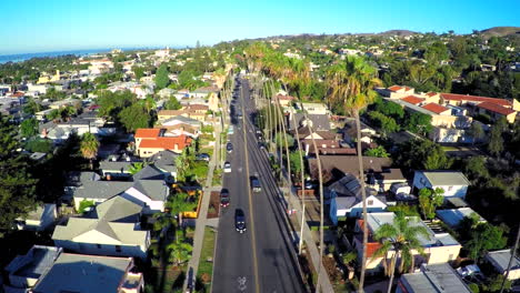 Toma-Aérea-Sobre-Una-Calle-Bordeada-De-Palmeras-En-El-Sur-De-California