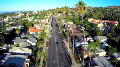 Toma-Aérea-En-Aumento-Sobre-Una-Calle-Bordeada-De-Palmeras-En-El-Sur-De-California