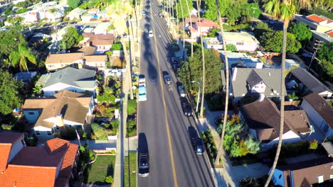 Beautiful-rising-aerial-shot-over-a-palm-tree-lined-street-in-Southern-California