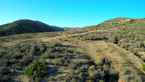Beautiful-aerial-shot-over-the-hills-of-Southern-California-with-a-hiker-walking-a-trail