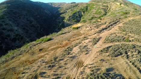 Aerial-shot-over-the-hillsides-of-Southern-California-with-a-hiker-below