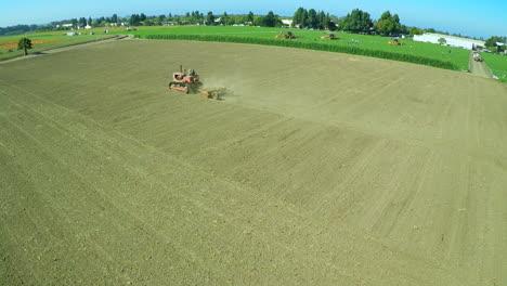 An-aerial-over-a-a-farm-worker-driving-a-tractor-across-barren-fields
