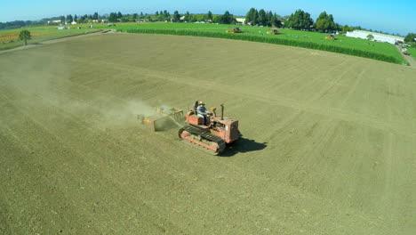 Una-Antena-Sobre-Un-Trabajador-Agrícola-Que-Conduce-Un-Tractor-A-Través-De-Campos-Estériles-1