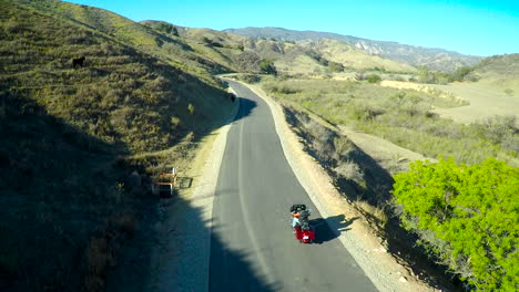 A-beautiful-aerial-shot-over-a-many-riding-his-Harley-motorcycle-on-the-open-road