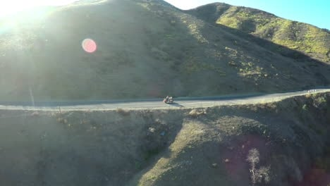A-beautiful-aerial-shot-over-a-many-riding-his-Harley-motorcycle-on-the-open-road-1