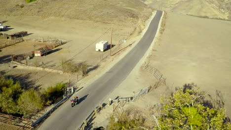 A-beautiful-aerial-shot-over-a-man-riding-his-Harley-motorcycle-on-the-open-road-1