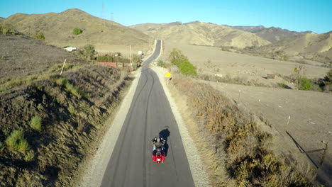 A-beautiful-aerial-shot-over-a-man-riding-his-Harley-motorcycle-on-the-open-road-2