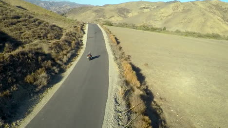 A-beautiful-aerial-shot-over-a-man-riding-his-Harley-motorcycle-on-the-open-road-5