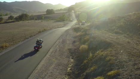 A-beautiful-aerial-shot-over-a-man-riding-his-Harley-motorcycle-on-the-open-road-and-into-the-sunset