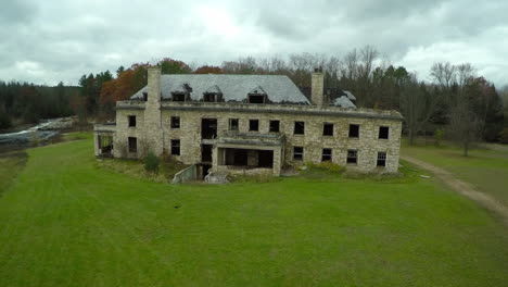 An-aerial-over-a-spooky-abandoned-mansion-in-the-countryside