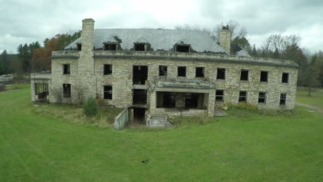 A-rising-aerial-over-a-spooky-abandoned-mansion-in-the-countryside