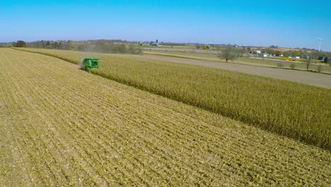 Excellent-aerial-over-a-rural-American-farm-with-corn-combine-harvester-at-work-in-the-fields