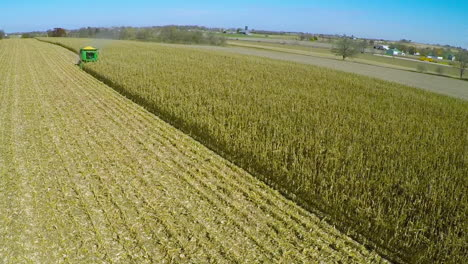 Excellent-aerial-over-a-rural-American-farm-with-corn-combine-harvester-at-work-in-the-fields-1
