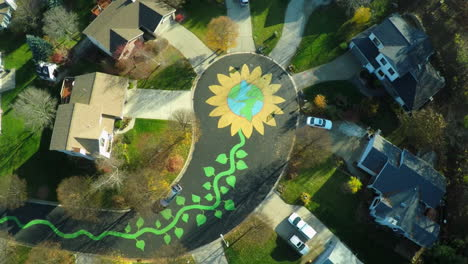 An-aerial-over-a-neighborhood-with-the-street-painted-as-a-large-flower