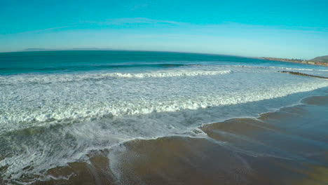 An-aerial-over-a-generic-beach-heading-out-to-the-ocean-with-large-waves-and-surf-breaking