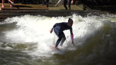 Surfers-brave-the-rapids-of-the-Eisbach-River-in-Munich-Germany-in-slow-motion