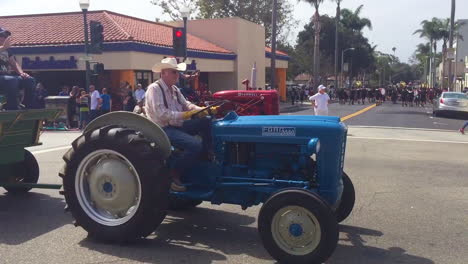 Farmers-drive-their-tractors-down-a-city-street-during-a-4th-of-July-parade-in-a-small-town