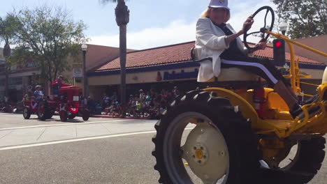 A-senior-lady-farmer-drives-her-tractor-down-a-city-street-during-a-4th-of-July-parade-in-a-small-town
