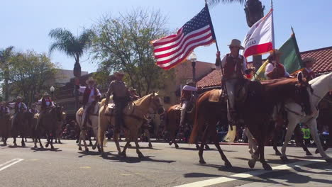 Cowboys-on-horseback-ride-through-a-small-town-during-a-4th-of-July-parade