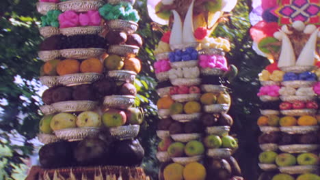 Balinese-women-with-high-offerings-walk-near-a-temple-in-Bali-Indonesia