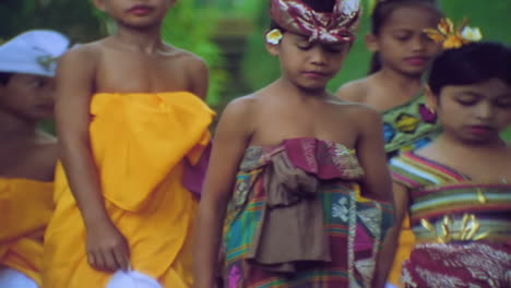 Children-walk-into-a-remple-in-Bali-Indonesia-during-a-religious-ritual