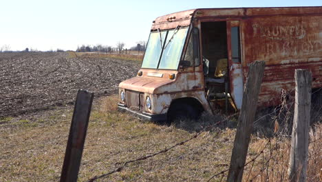 An-abandoned-delivery-truck-sits-in-a-plowed-field-in-the-Midwest