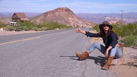Una-Mujer-Autoestopista-Intenta-Dar-Un-Paseo-Junto-A-La-Carretera-En-El-Desierto