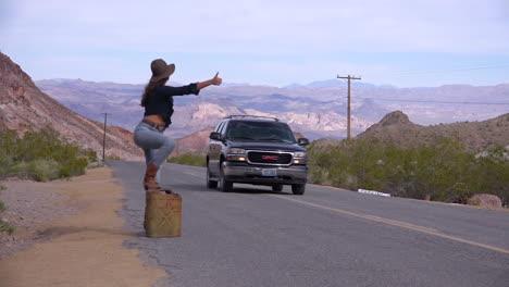 Una-Mujer-Autoestopista-Intenta-Dar-Un-Paseo-Junto-A-La-Carretera-En-El-Desierto-Después-De-Quedarse-Sin-Gasolina-1