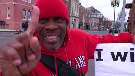 A-man-holds-up-an-antiTrump-rally-sign-saying-I-Will-Not-Shut-Up-And-Dribble-on-an-American-street-corner