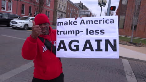 A-man-holds-up-an-antiTrump-rally-sign-saying-Make-America-Trump-less-Again-on-an-American-street-corner