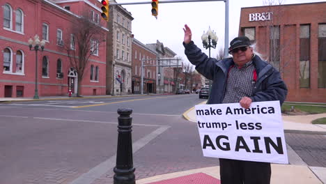A-man-holds-up-an-antiTrump-rally-sign-saying-Make-America-Trump-less-Again-on-an-American-street-corner-1