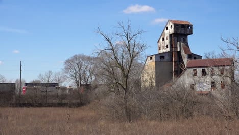 Freight-train-passes-an-old-abandoned-rusting-mill-or-factory-suggests-the-end-of-America-as-an-industrial-power