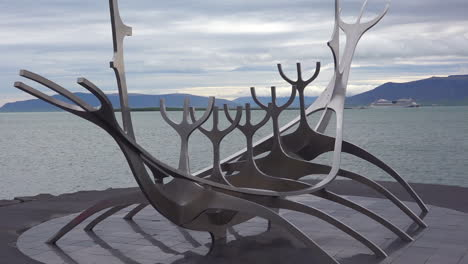 A-sculpture-of-a-viking-ship-stands-at-Reykjavik-Iceland-harbor-with-cruise-ship-background