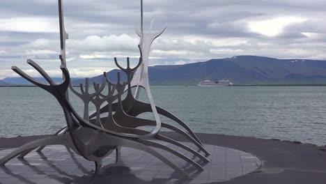 Una-Escultura-De-Un-Barco-Vikingo-Se-Encuentra-En-El-Puerto-De-Islandia-En-Reykjavik-Con-Un-Crucero-De-Fondo-1